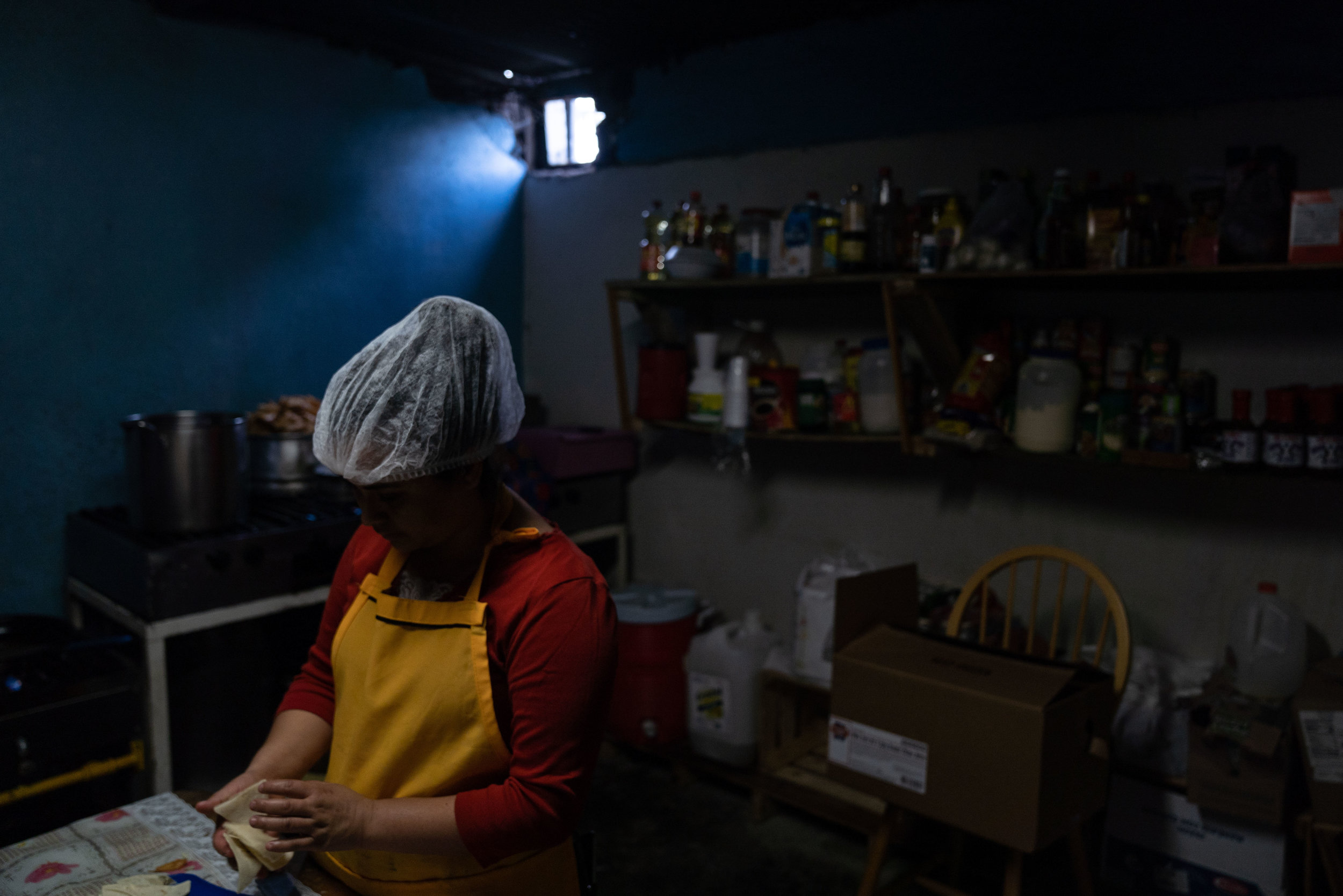 """A migrant who was returned to Mexico under the """"Remain in Mexico"""" policy prepares a meal at a shelter in Tijuana in May, 2019."""