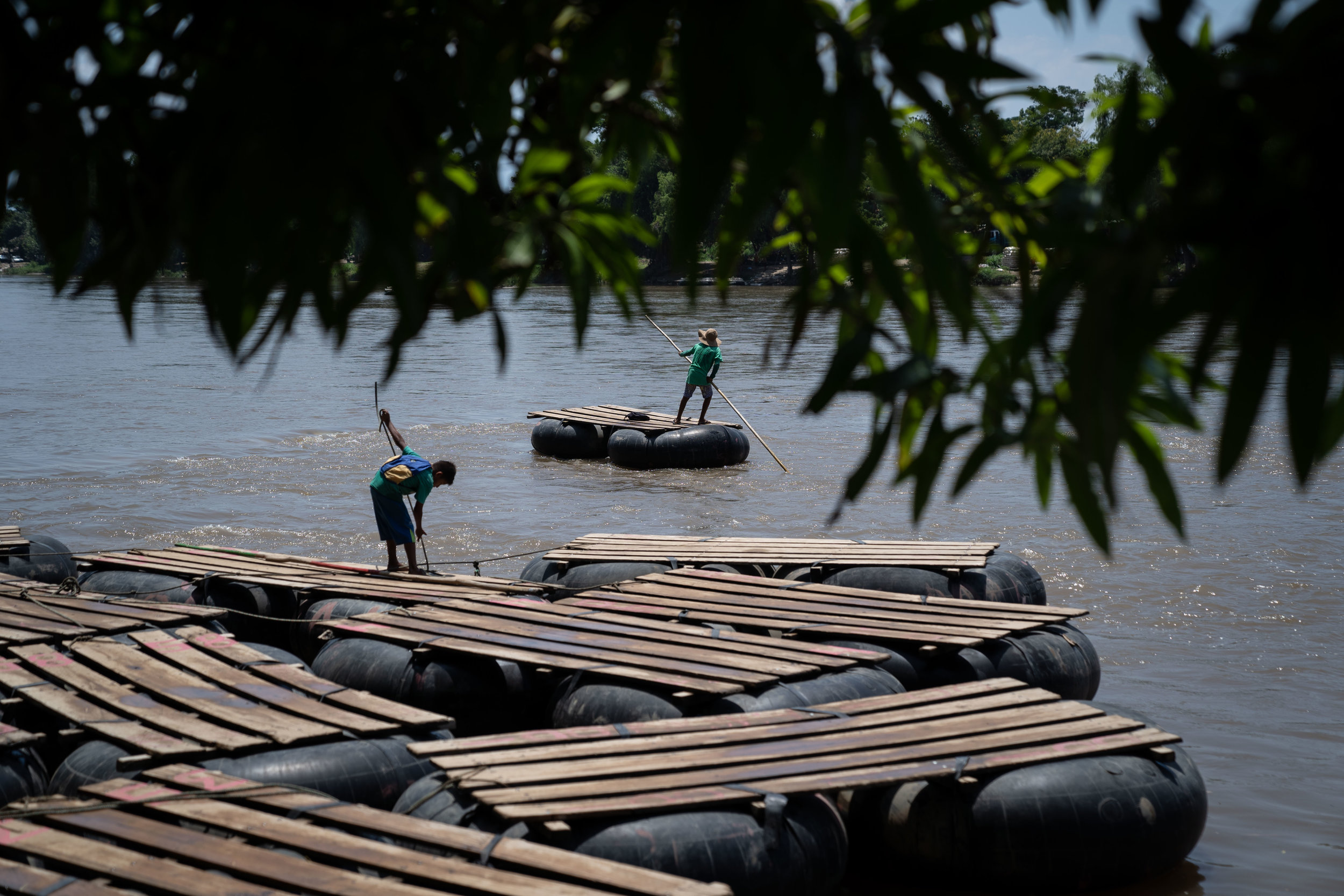 Men stand on makeshift rafts on the Suchiate River on the Guatemala-Mexico border, on June, 2019.