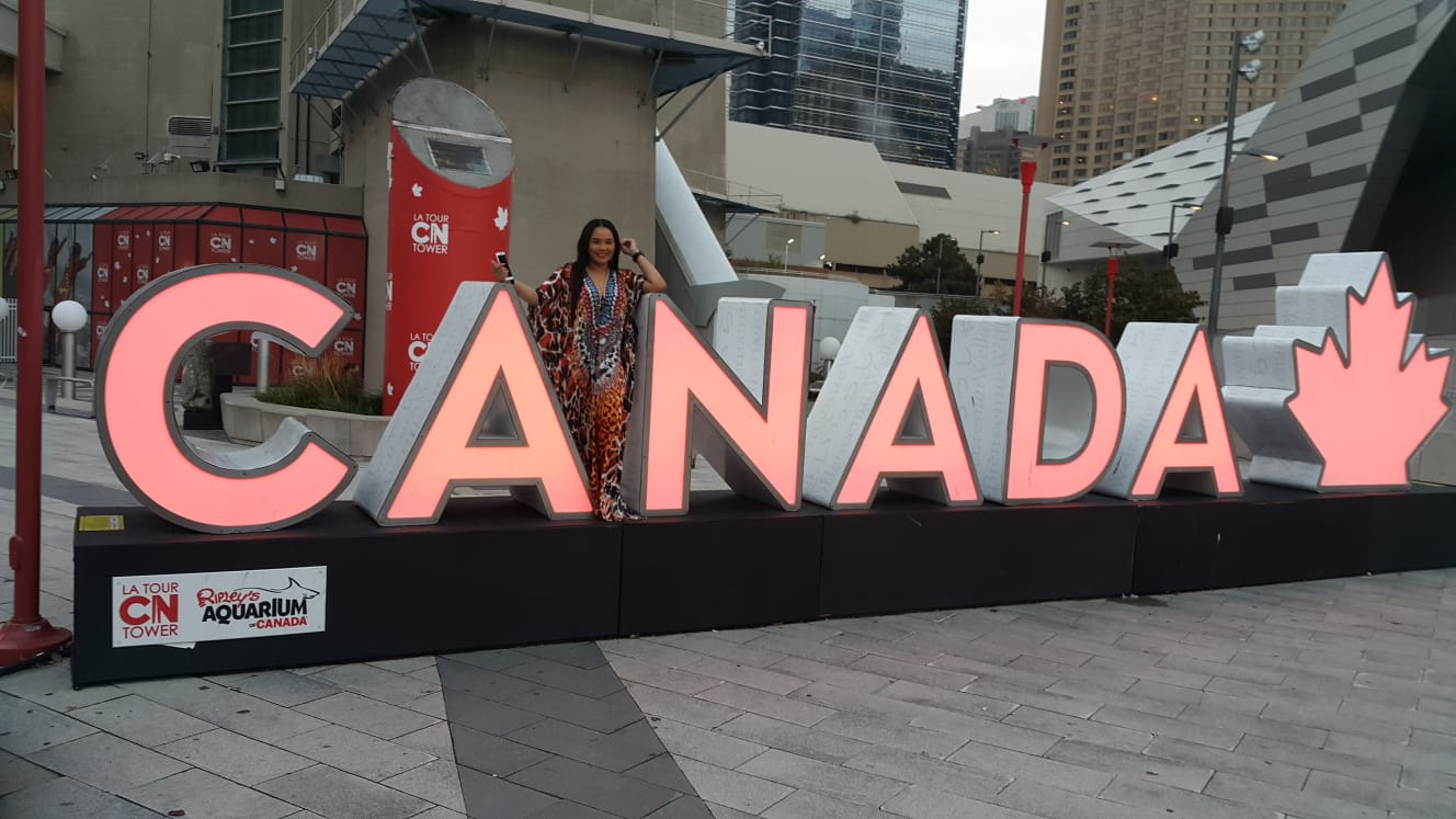 Leanna Ryce posing with the 3D Canada Sign by the CN Tower, Toronto, Ontario, Canada.