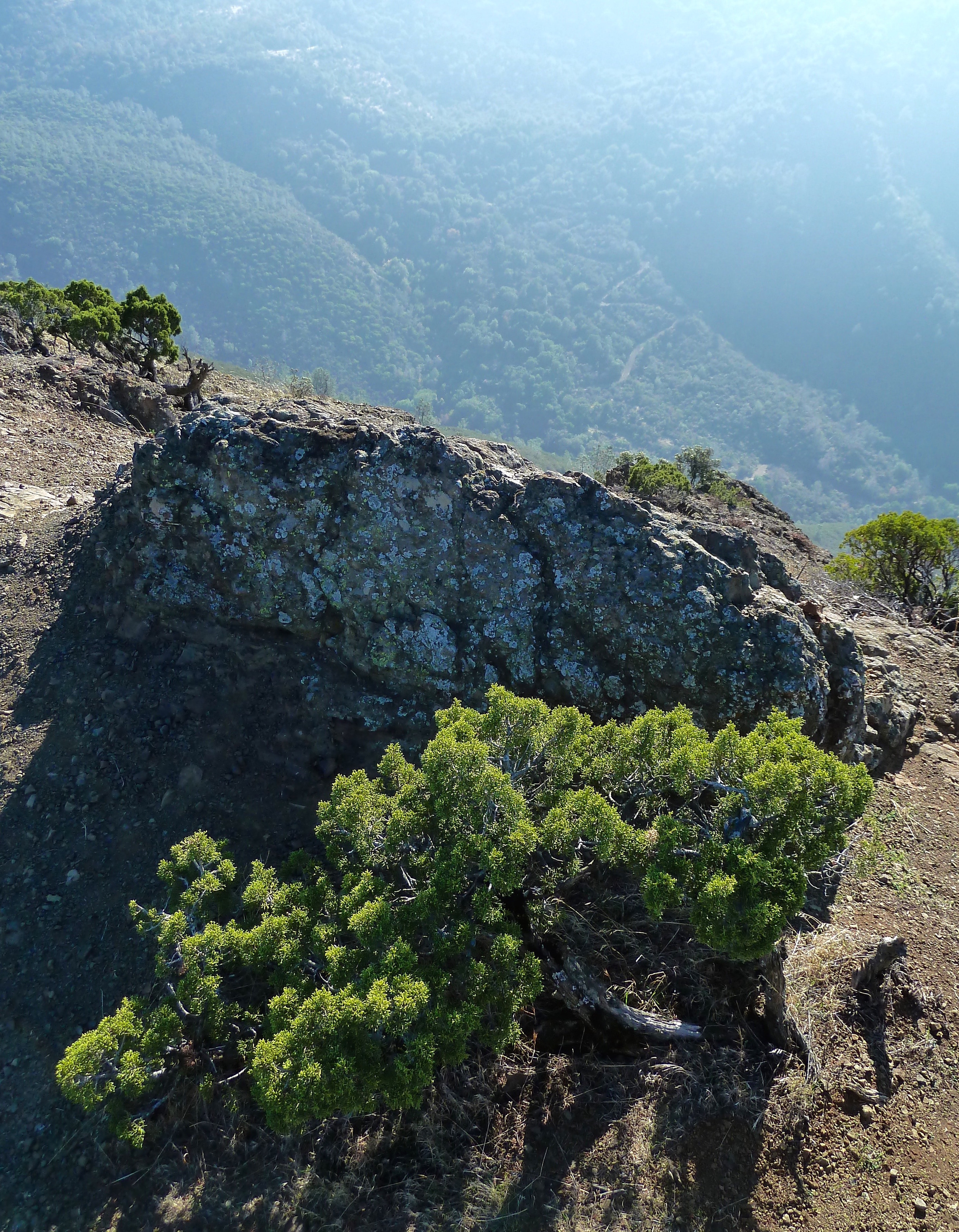 A rock atop Eagle Peak mimics the trapezoidal shape of the entire peak. Below, Mitchell Canyon Road snakes up toward Deer Flat.