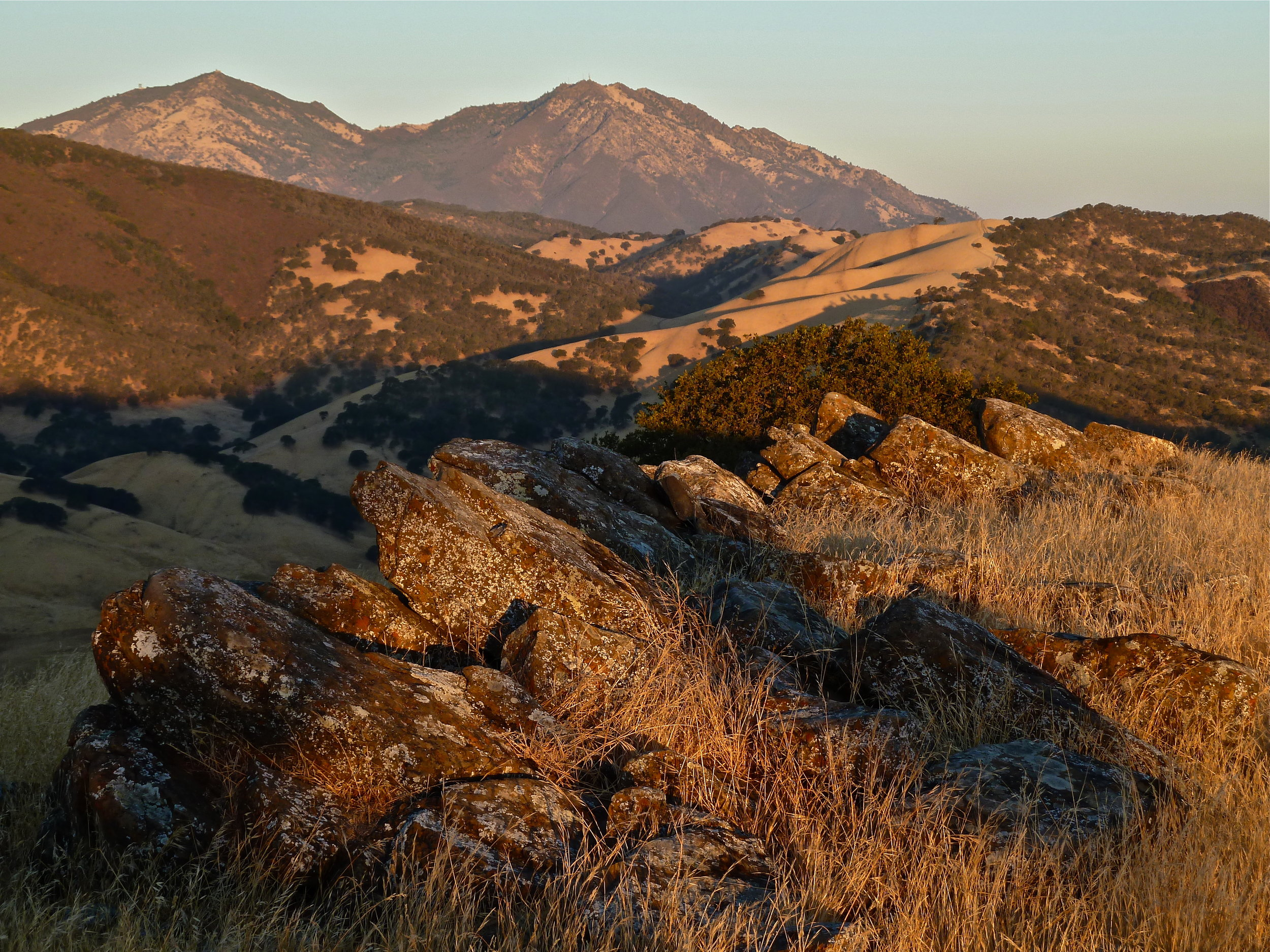 A warm summer sunrise strikes Round Valley's Castle Ridge. Eight miles northwest rises Mt. Diablo.