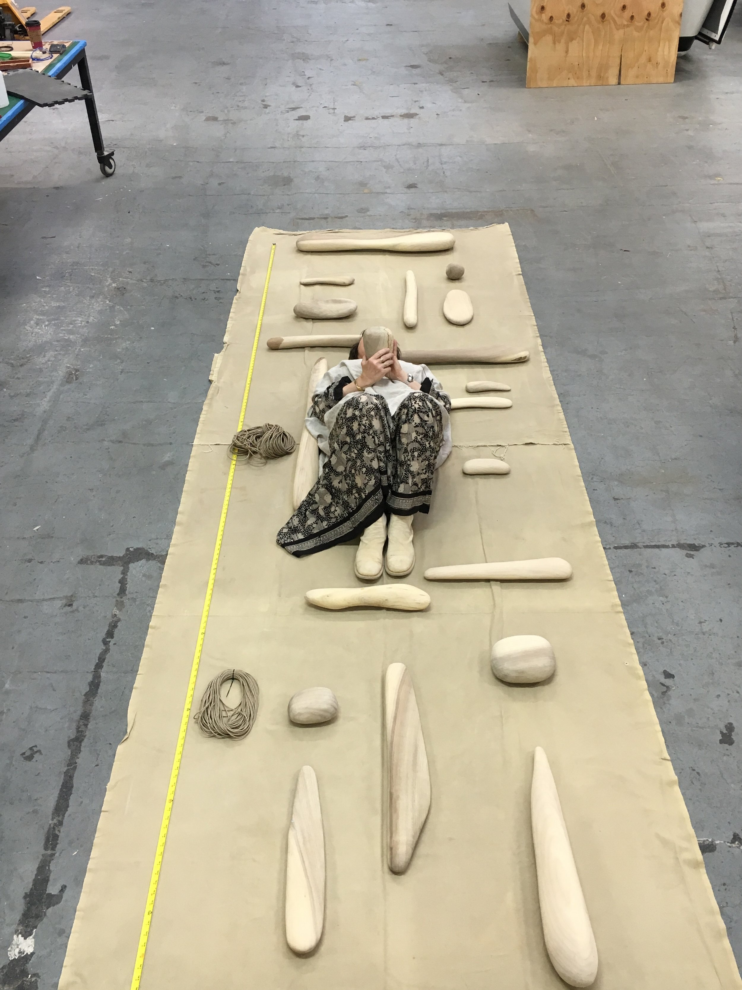 Ruth Kneass laying with the meticulously sculpted pieces of her Bay Tower mobile. © Ruth Kneass
