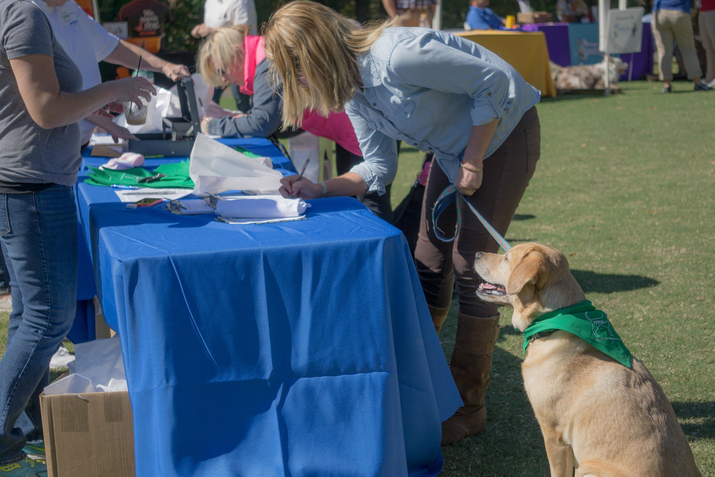 Yellow lab and his mom registering for Mutt Strutt