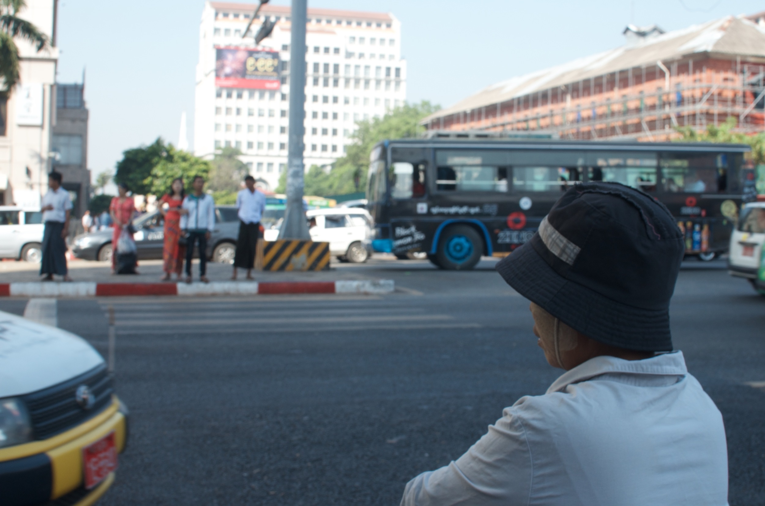 An old woman waiting to cross on the busy Bogyoke Aung San Road.