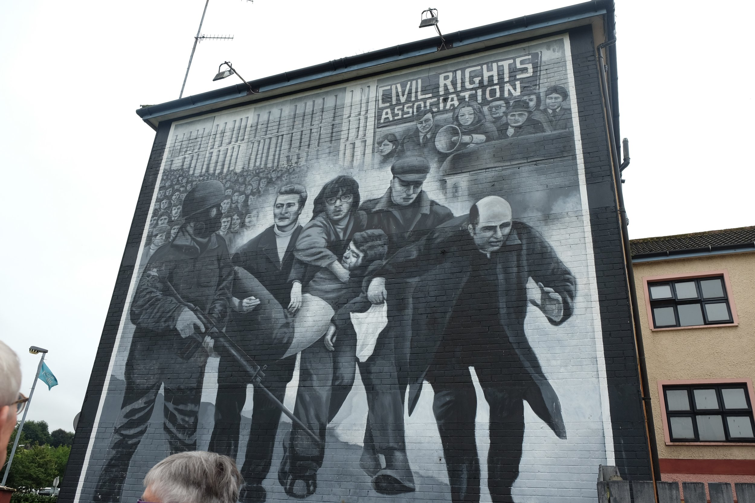 """Bloody Sunday Mural, unveiled on January 30, 1999 during the 25th anniversary of the events that occurred on that day. British soldiers shot into a crowd of unarmed civilians and 14 people died. What you see is a local Catholic priest (later identified as Bishop Daly) carrying the body of Jack Duddy from the scene. Not pictured is the bottom portion of the mural, which depicts a bloodstained """"civil rights"""" banner, used to cover one of the bodies."""