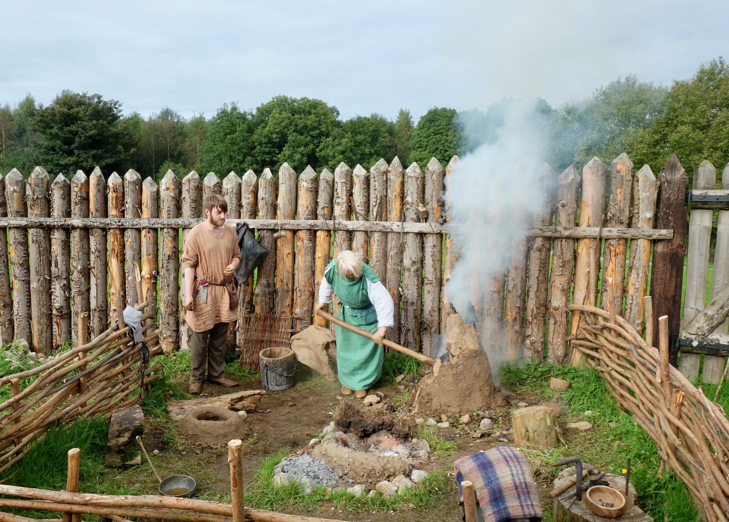 Teaching us how to make charcoal.