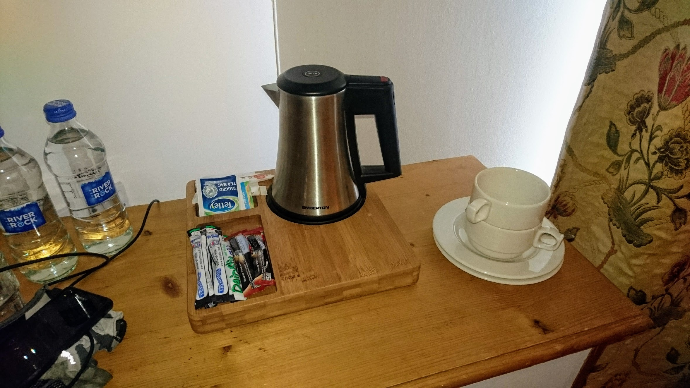 """A kettle (or """"water boiler thingy"""", as a certain American bewildered by this advanced technology calls it), complete with tea sachets, two mugs, sugar, cream, and milk. People in the UK love their tea - entire books on British social behaviour have been written around this beverage."""