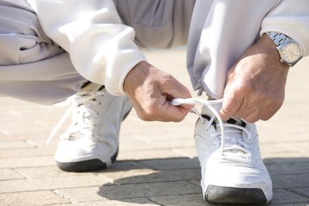 47076551_S_man_senior_exercise_sneakers_watch_tie_laces_bend.jpg