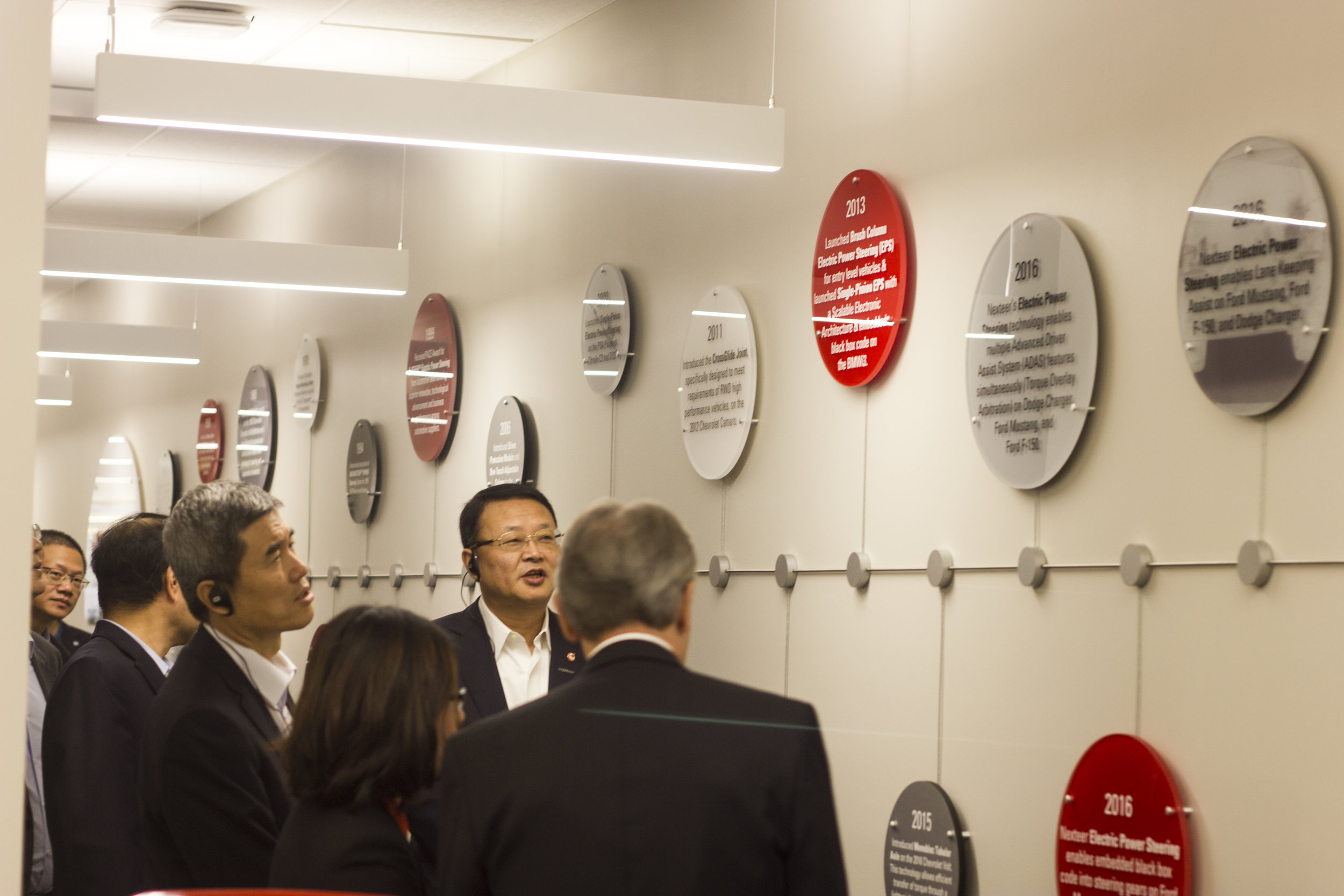 Nexteer president & board viewing the  Timeline of Innovation installation I designed and produced for the Nexteer Auburn Hills World Headquarters.