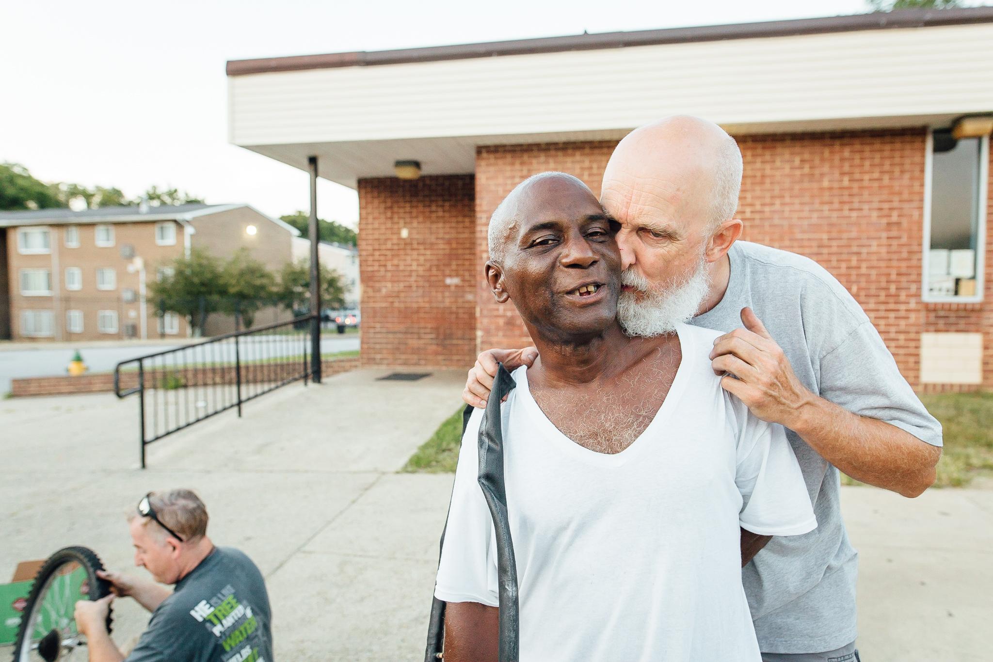 Older caucasian man hugging older african american man.jpg