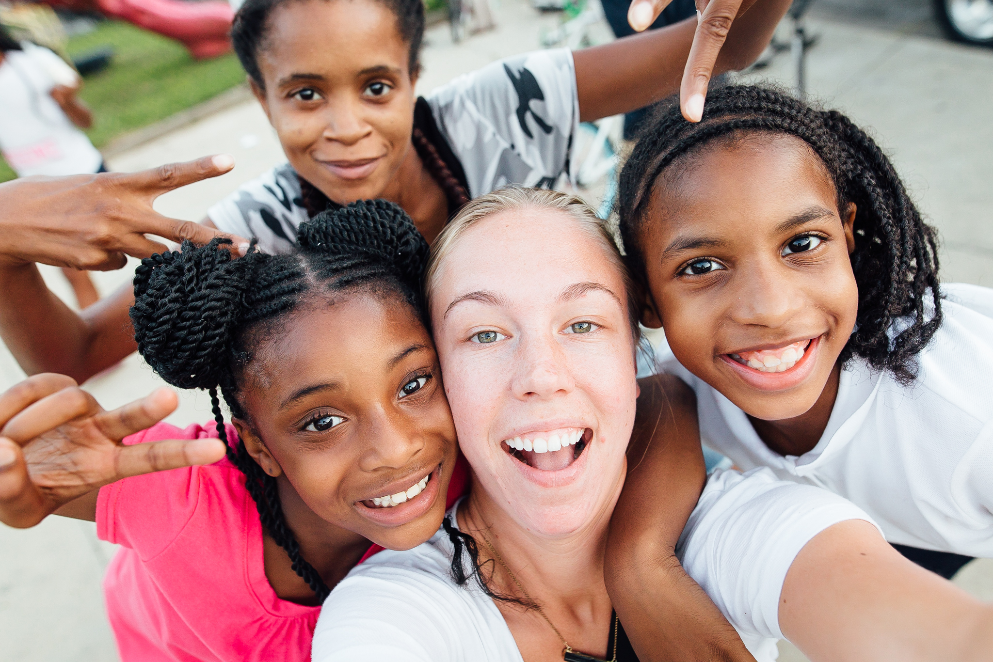 young adult girl smiling selfie with three younger african american girls hands peace signs.jpg