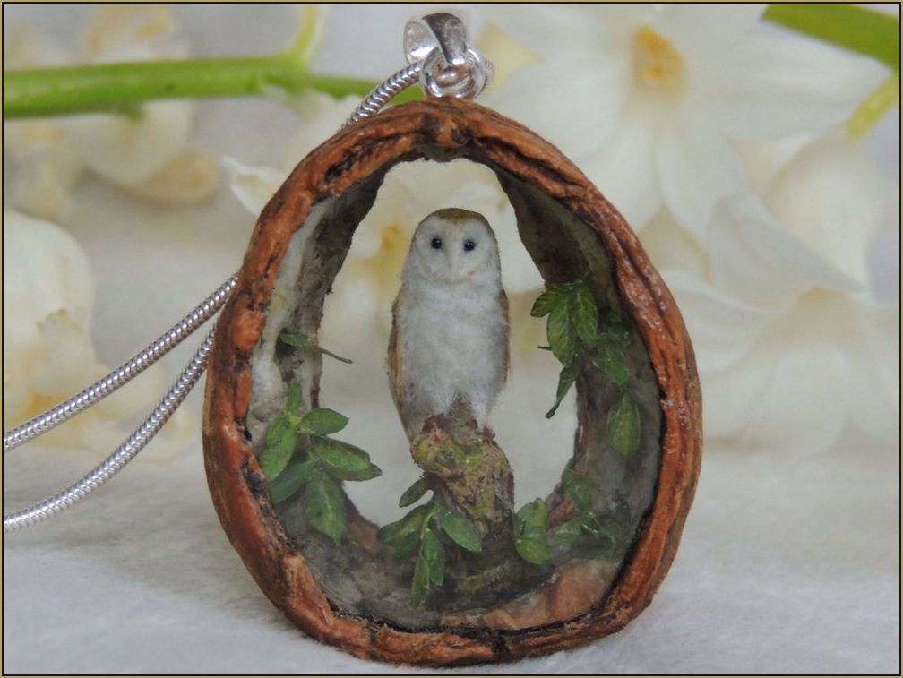 A high detailed miniature barn owl sculpture set inside a walnut pendant.    Arranging the unique design for the pendant is determined by working with the natural shape of the walnut shell. The interior is decorated with hand painted miniature walnut leaves.    Both the front and back apertures are sealed with hand cut crystal glass.    Sterling Silver hoop bail    Pendant Dimensions: Pendant 3.5 cm at the highest point (excluding bail), 3.2 cm across the widest point 1.2 cm Depth.    Barn owl dimensions: 1.5 cm approx    Please request to join the    mailing list    to be notified when new pendants will be available for purchase.    Design: Anya Stone