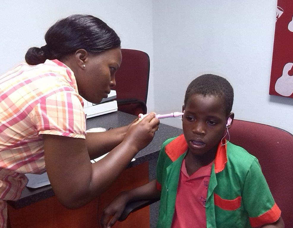 Above : A hearing aid test and application at Glad Tidings Orphan Care centre.