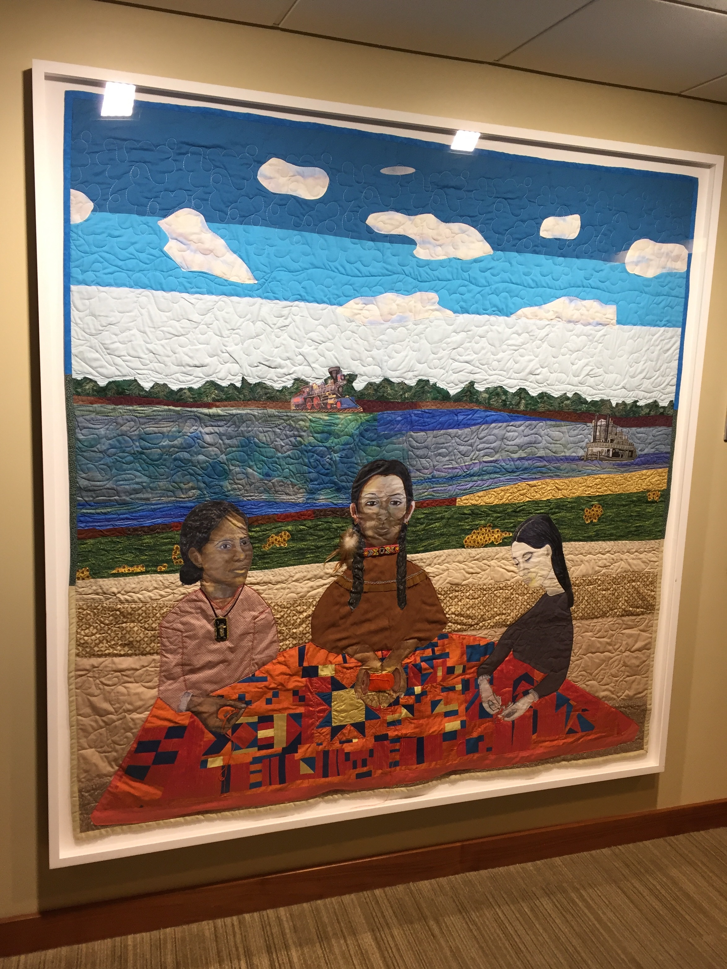 NedRa Bonds  Connecting Threads, 2014  A beautiful quilt showing 3 women of different ethnicities all working together on a quilt.