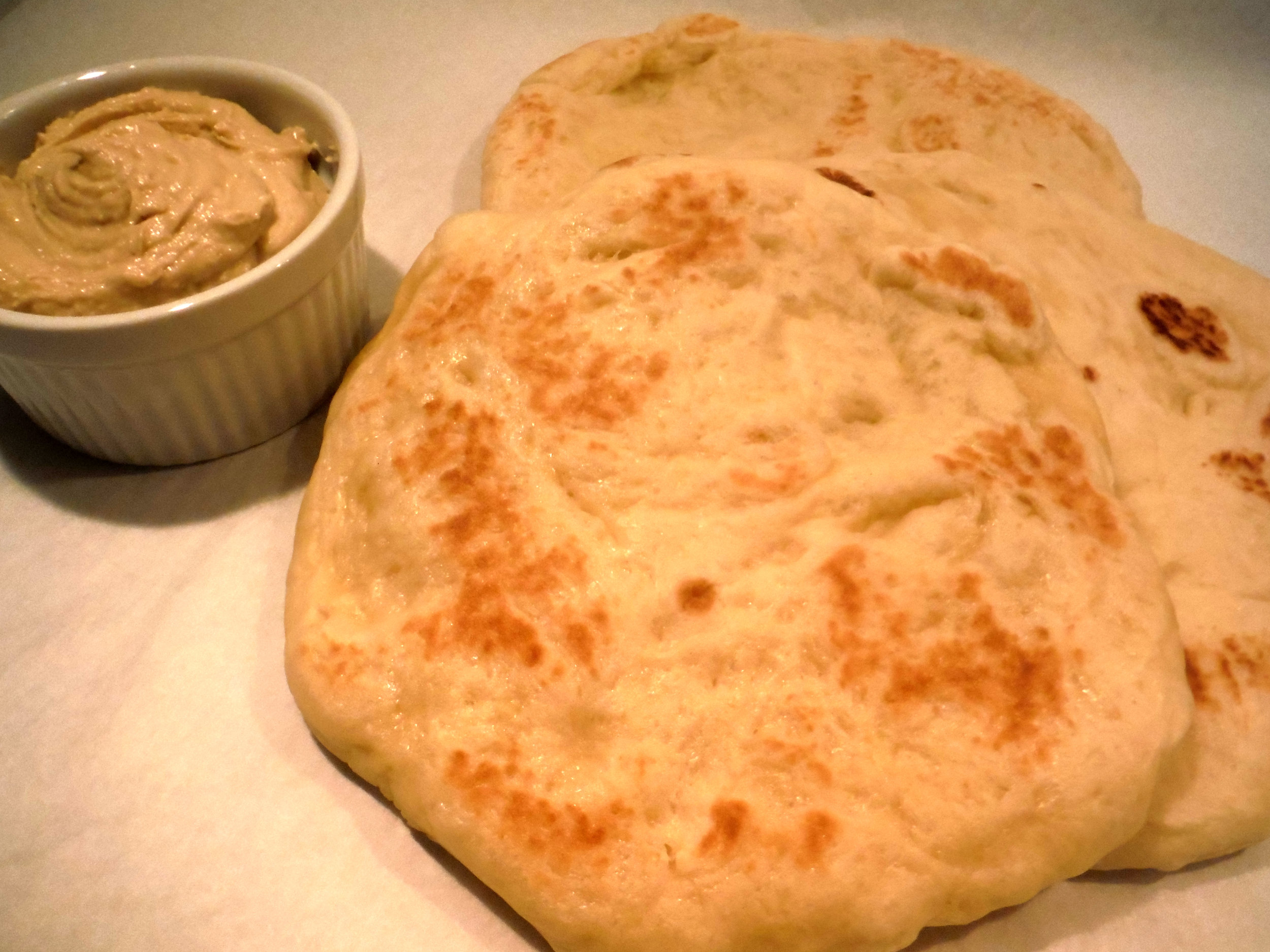 Naan   Our hand formed naan is soft and chewy, and perfect for dipping, pizza crust (grilled pizza!), or an unconventional PB&J! $6 per dozen