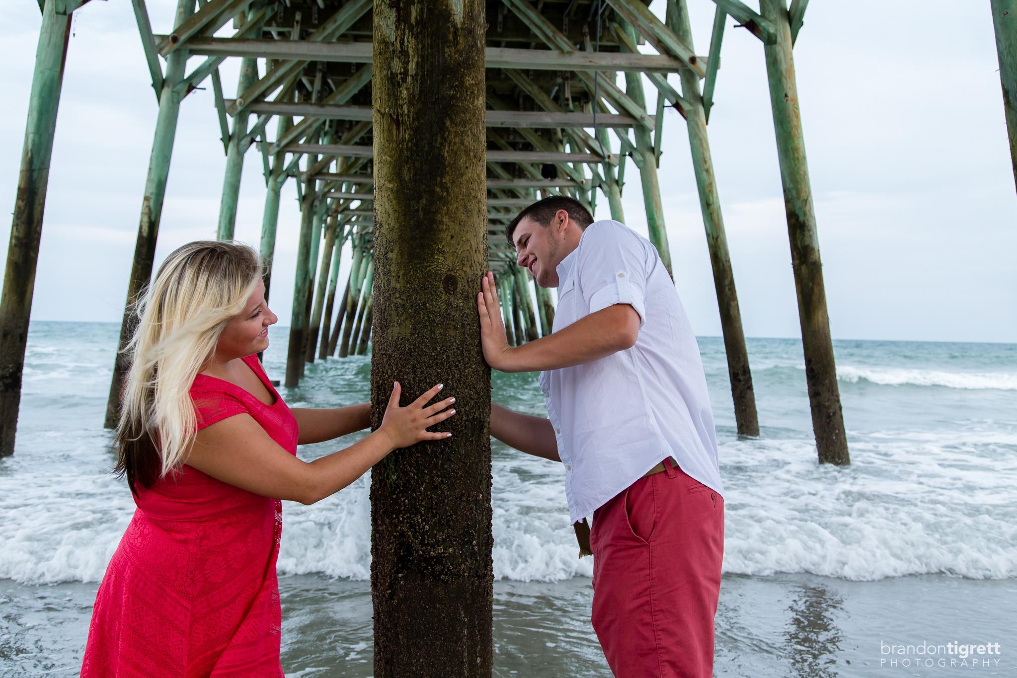 Playful bride and groom under pier
