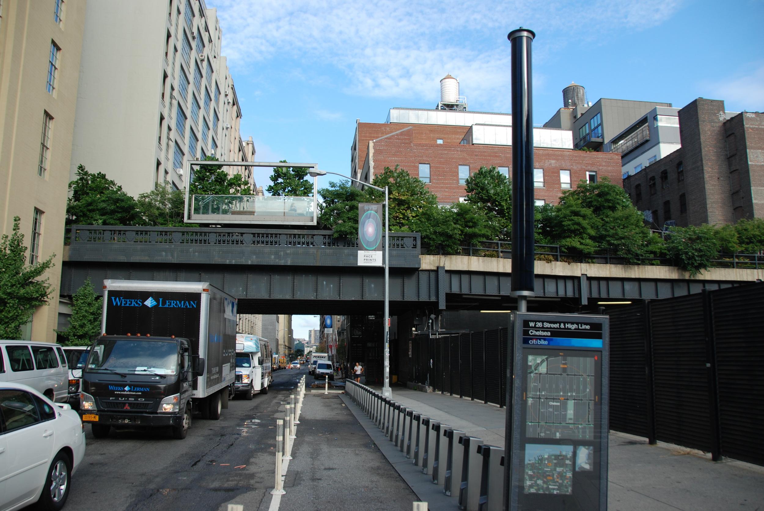 Stromy nad ulicí 23 St na Manhattanu. Nad mostovkou je dobře patrné jedno z vyvýšených posezení, na němž se mohou lidé posadit a pozorovat dění v ulici pod nimi. (foto: Libor Hinčica)