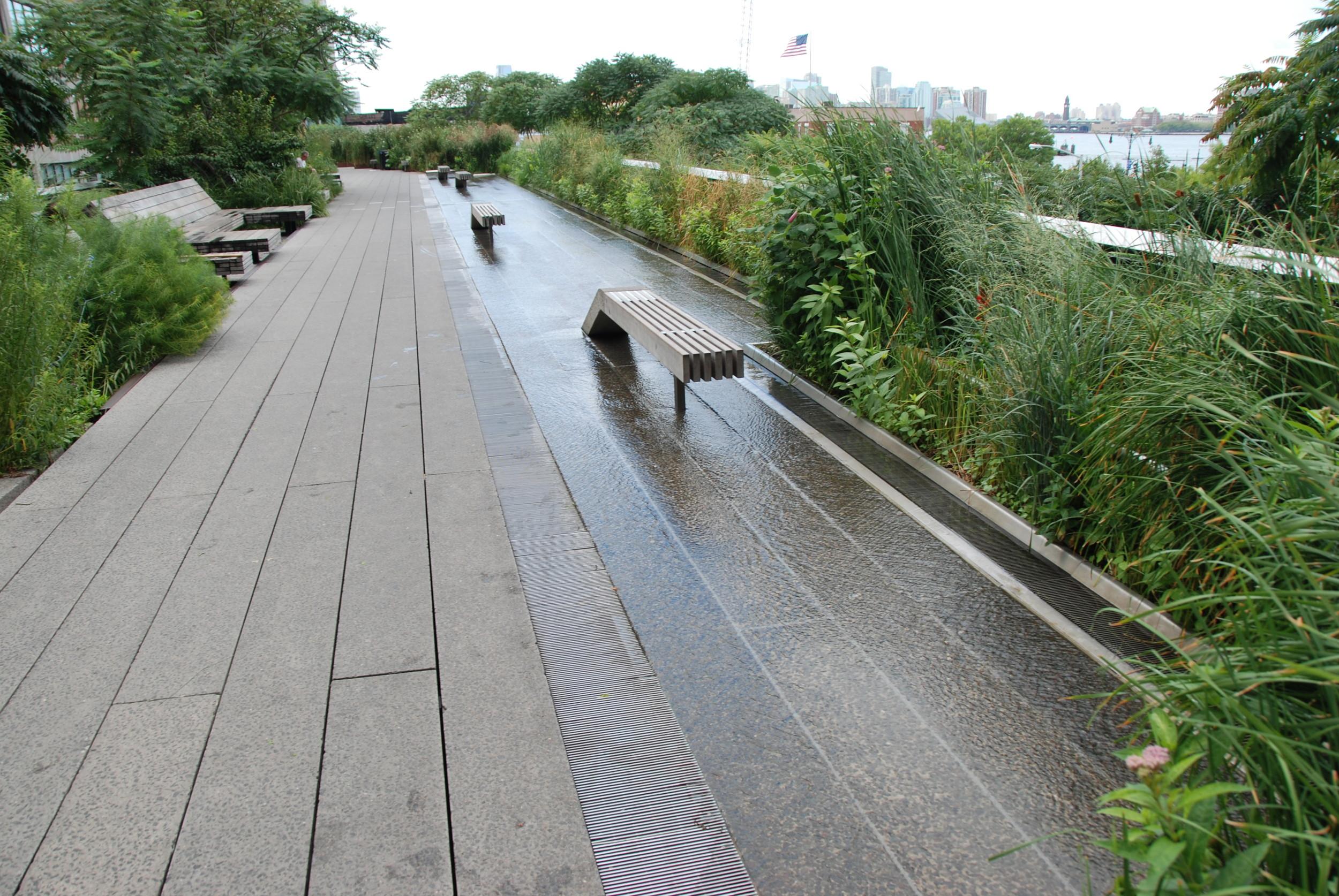 Tato část High Line patří mezi nejpopulárnější, a to nejen pro možnost procházky v tekoucí vodě. Jedná se o široký prostor (za zalení napravo se nachází další část High Line s další zelení) v blízkosti občerstvení, toalet a s možností využití lehátek (na levé straně fotografie), odkud můžete pozorovat řeku Hudson a New Jersey. (foto: Libor Hinčica)