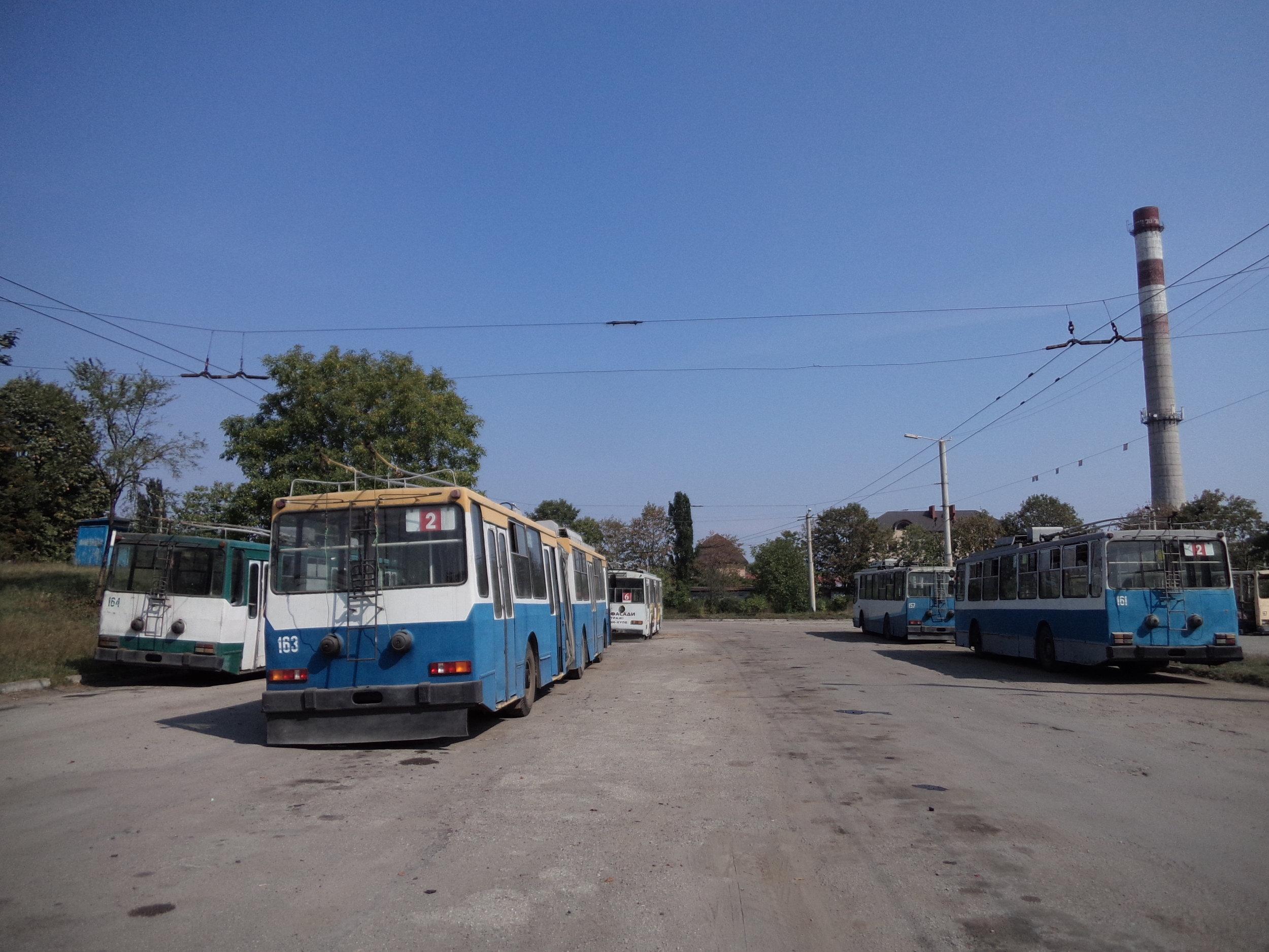 V polovině 90. let přišly do Ivano-Frankivsku čtyři článkové vozy JUMZ T1, které obdržely ev. č. 161–164. Vozům ev. č. 161 a 164 byla později odňata zadní část a po příslušných úpravách se z nich staly sólo trolejbusy vedené pod stejnými ev. č., avšak už jako přeznačený typ JUMZ T1P. Oba tyto zkrácené vozy jsou přitom na snímku přítomny. Z dvou zbývajících článkových vozů jezdí už jen jeden, a to ten nesoucí ev. č. 163. Na pravé straně vzadu si ještě povšimněme vozu s ev. č. 157. Jedná se o jeden ze sedmi krátkých vozů (ev. č. 157, 165–170) typu JUMZ T2, které do Ivano-Frankivsku zavítaly ve stejném období jako vozy článkové. Dnes už jsou vypravovány jen tři z nich.