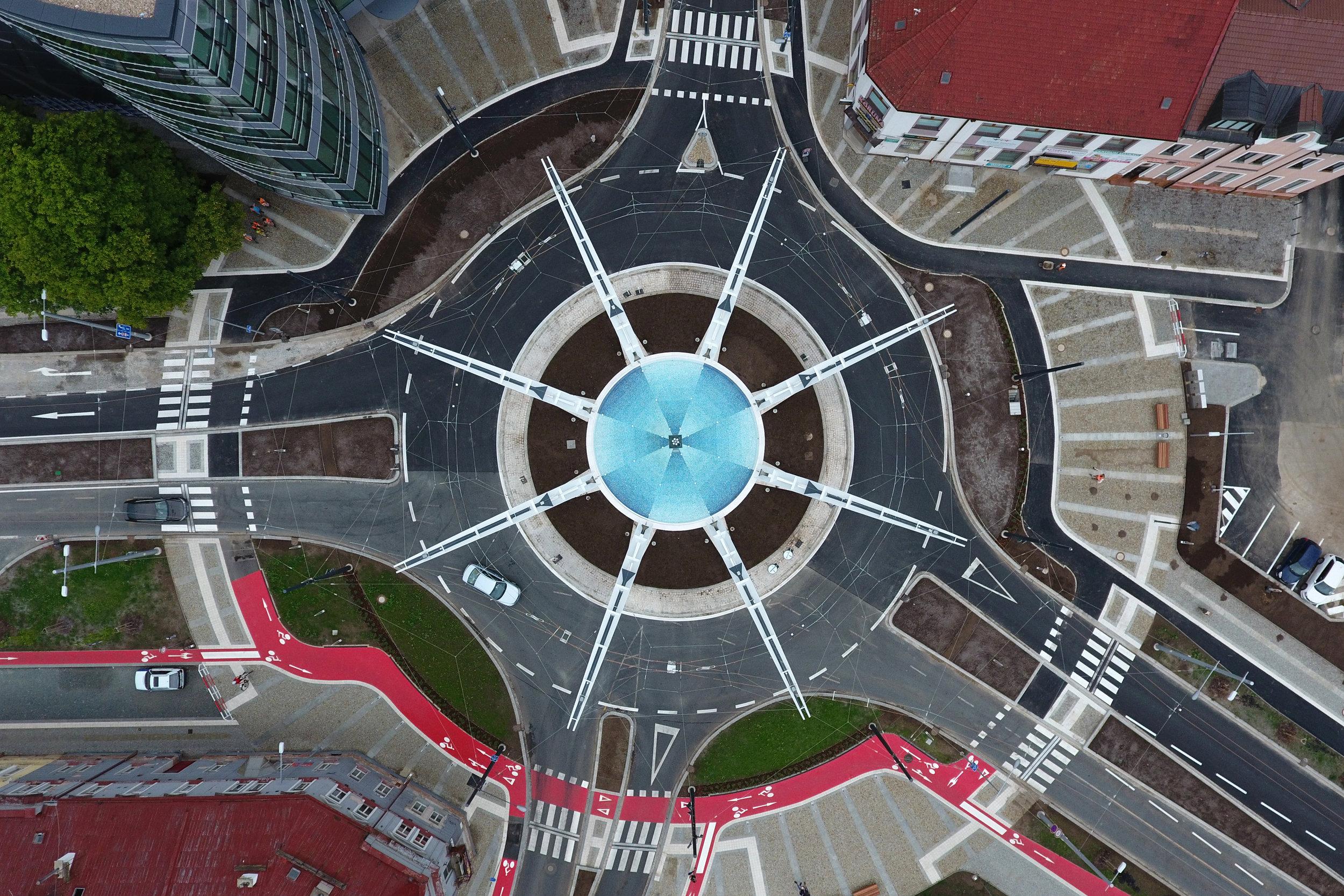 Křižovatka U Koruny v Hradci Králové pracuje významně s motivem kruhu. Prakticky veškeré součásti byly navrženy tak, aby tvořily dokonalou kružnici. To platí i pro trolejové vedení, které zavěsila společnost Elektrizace železnic, přičemž muselo být použito několik inovací na to, aby bylo požadovaného kruhového tvaru trolejového vedení dosaženo. Podrobně jsme se této stavbě věnovali v čísle 3/2016. (foto: atelier Patrika Kotase)