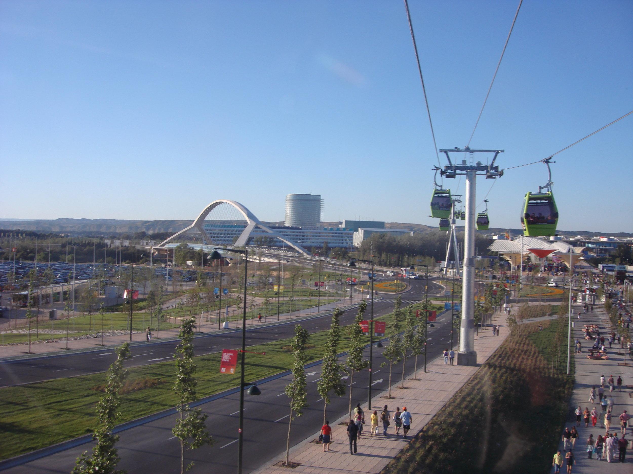 """Lanová dráha, jejímž dodavatelem byla společnost Leitner, měla lineární dráhu a vedla od nádražíDelicias (nejde vidět, po levé ruce fotografa) k areálu Expa.Nalevo od lanovky spatříme ve stejném roce (2008) otevíranýmost  Puente del Tercer Milenio , jehož autorem je Juan José Arenas de Pablo, t. č. 76letýrodák z nedaleké Huescy, a za mostem vidíme dnes opuštěnou """"Vodní věž""""."""