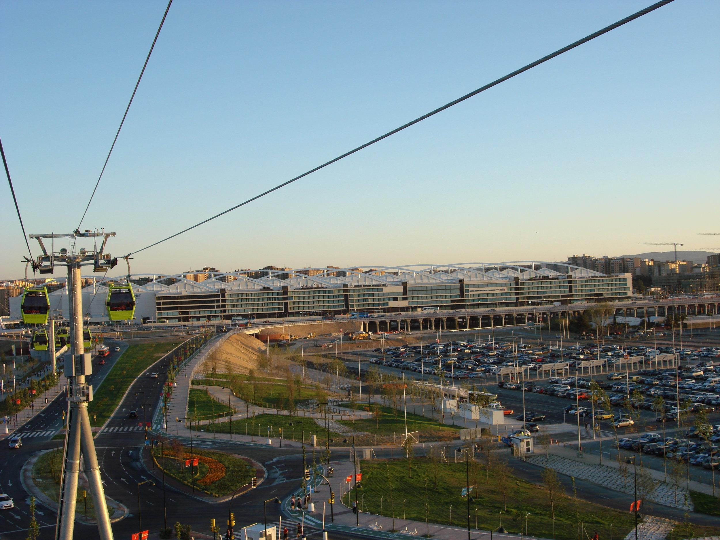 """Pohled na intermodálnístanici Delicias, kde se potkávají vysokorychlostní i konvenční vlakové spoje, ale i autobusy. Jedná se o pozoruhodnou, nicméně ne praktickou stavbu, která si vyžádala obří investici. Vzhledem k tomu, že nedaleký výstavní areál dopomohl nejen k lepšímu obrazu města, ale i kapsám politiků a jim spřátelených osob,a pak po třech měsících slávy začal vadnout, neváhaly některé noviny přijít s články typu  """"lanovka, která spojuje mrhání peněz s ruinou"""" ."""