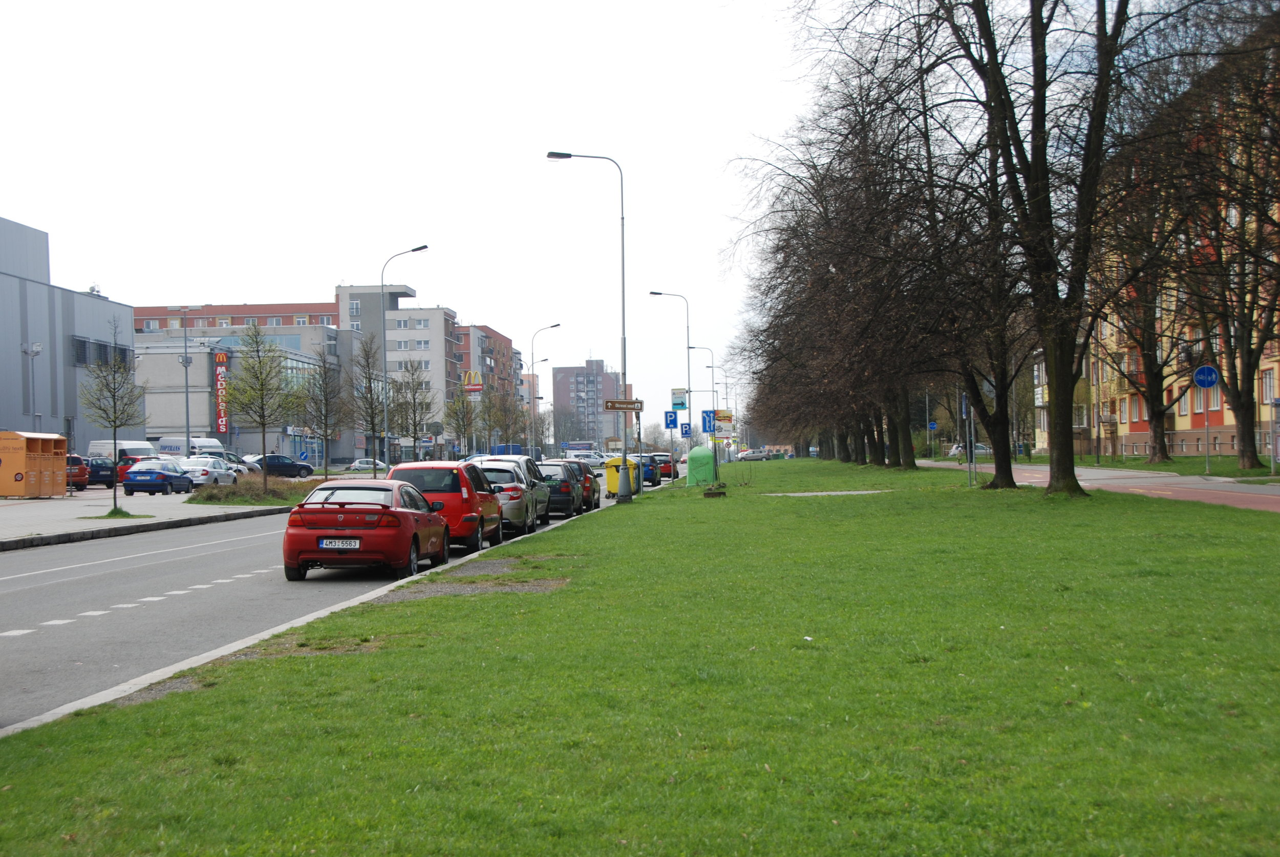 Opačný pohled na ulici Francouzskou a rozsáhlý pás zeleně. Nalevo jde vidět část zástavby vybudované z větší části po roce 1990. Namísto reprezentativního náměstívznikla obytná zástavba, obchodní středisko a hypermarket. Šance na důstojné propojení dvou stavebních obvodů Poruby byla ztracena.(foto: Libor Hinčica)