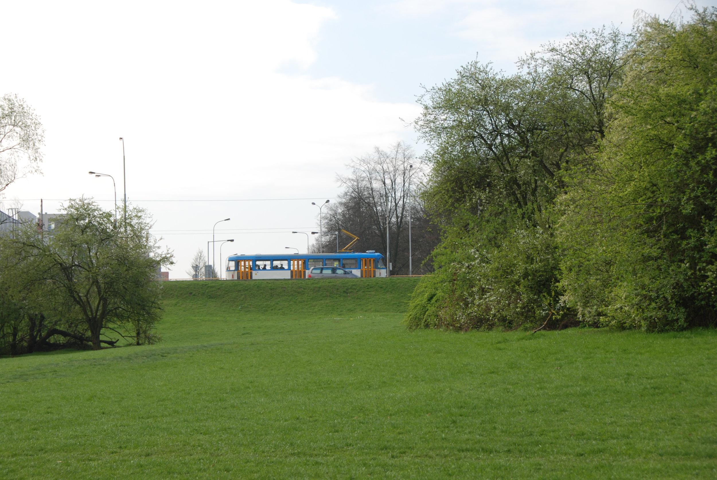 Opačný pohled než na předchozí fotografii. Z tohoto snímku je zřetelný značný výškový rozdíl mezi koridorem vyhrazeným pro tramvaj, a vyvýšeným náspem ulice Opavské, po němž právě projíždí vůz typové řady T3. Ve svahu měl začínat/končit tunel prvního podzemního úseku ostravské tramvaje, který se nikdy nerealizoval.(foto: Libor Hinčica)