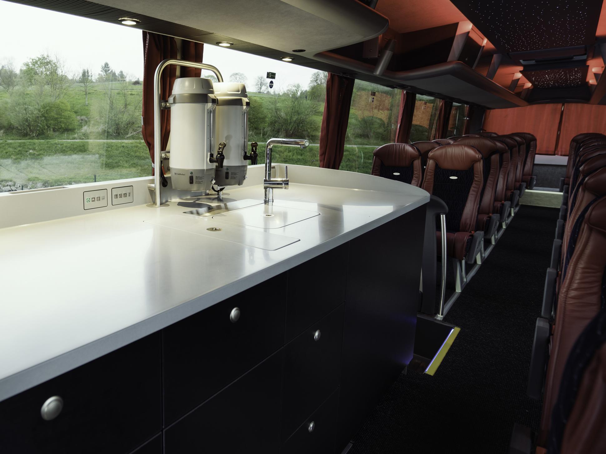 Moderní kuchyňský pult před druhými dveřmi se světleným logem v pracovní desce. (foto: MAN Truck & Bus)