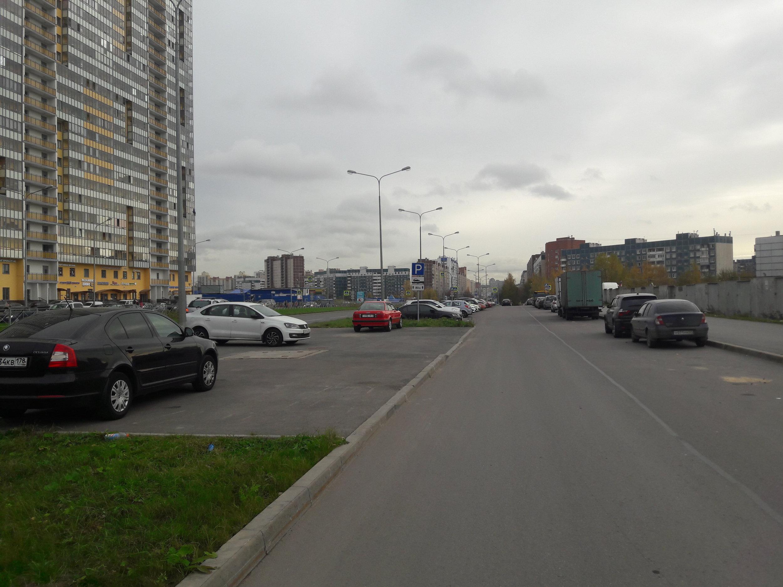 Parašutnaja ulica při pohledu na jih. Po ní směřují trolejbusy linky č. 2 k obchodnímu centru, u kterého se otočí, a směřují zpět na sever, akorát již po paralelně vedeném Komendantskom prospektu a už pod dráty.