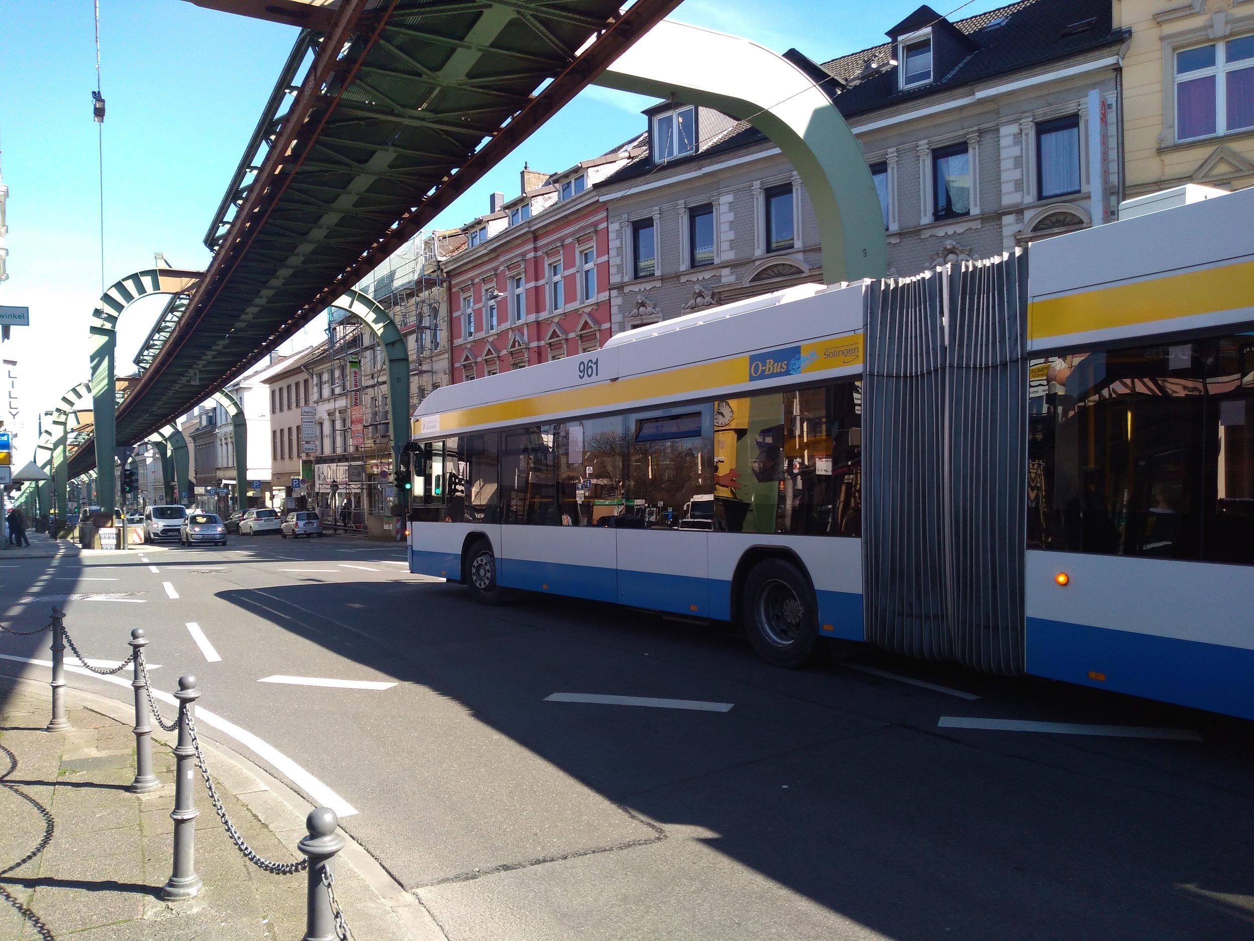 Trolejbus kdysi po příjezdu do Wuppertalu dojel k výchozí zastávce místní slavné visuté dráhy (za zády fotografa) a vracel se zpět. U visuté dráhy byla trojúhelníková bloková smyčka, na které trolejbusy měnily směr. Dne 4. srpna 2014 začaly trolejbusy jezdit k vohwinkelskému nádraží s pomocí dieselového pohonu a velká část smyčky, ze které trolejbus právě vyjíždí, tím zůstala nevyužita.