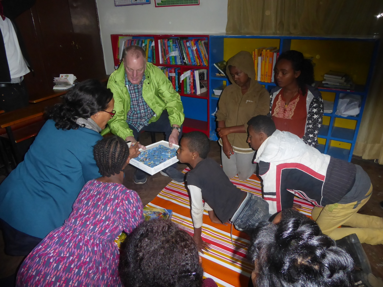 George showing the children at BHE puzzles and board games