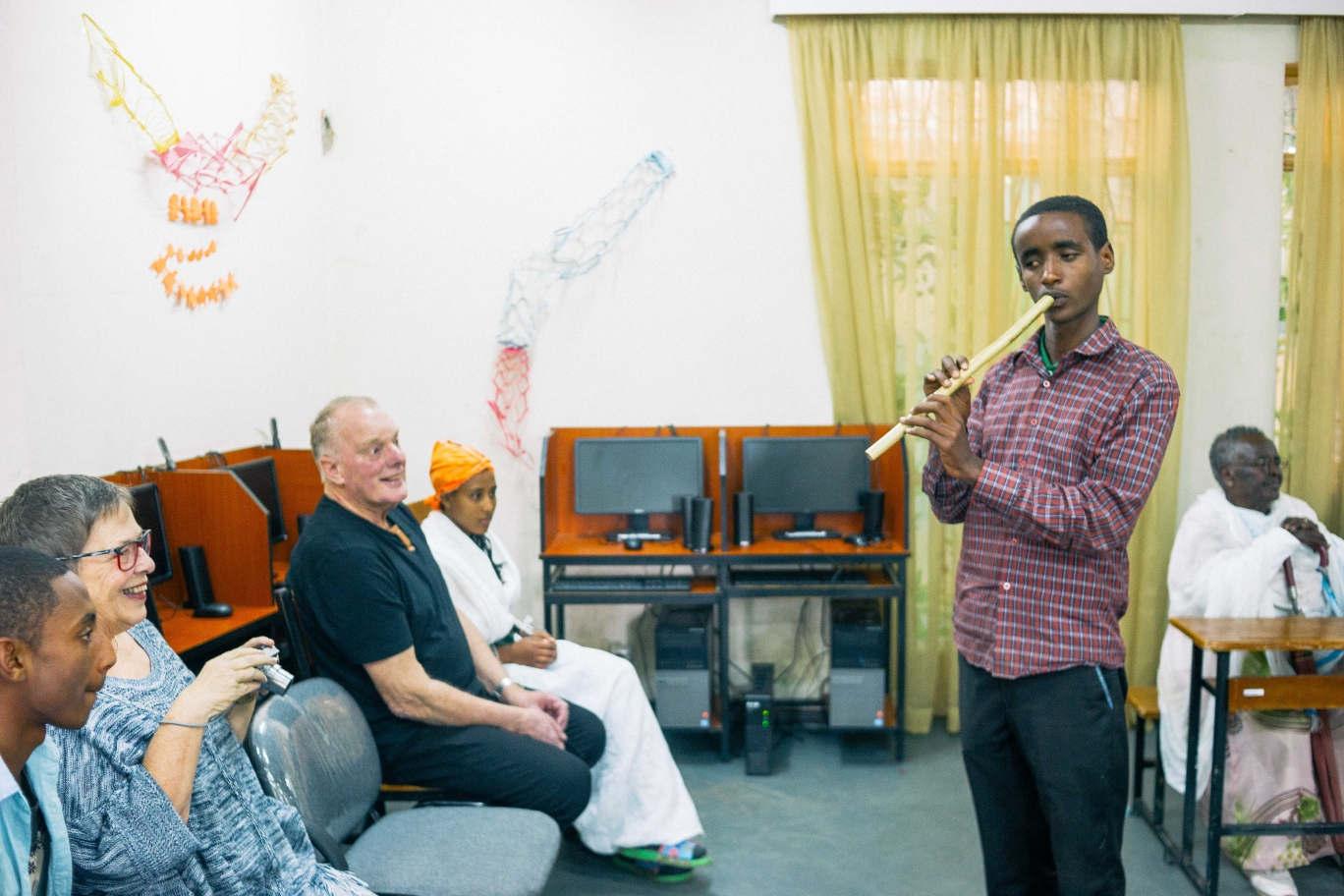 Biruh, a youth who is visually impaired playing the flute