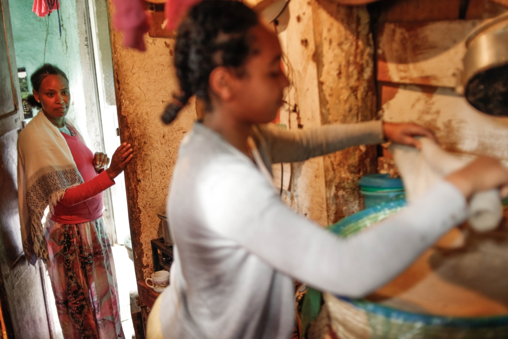 Photo by Mekbib Tadesse    Favon supporting her guardian Bizunesh with chores. Favon lost her parents and Bizunesh was there for her ever since. Favon is in tenth grade and helps Bizunesh with her small business selling coffee and snacks to cover their needs.