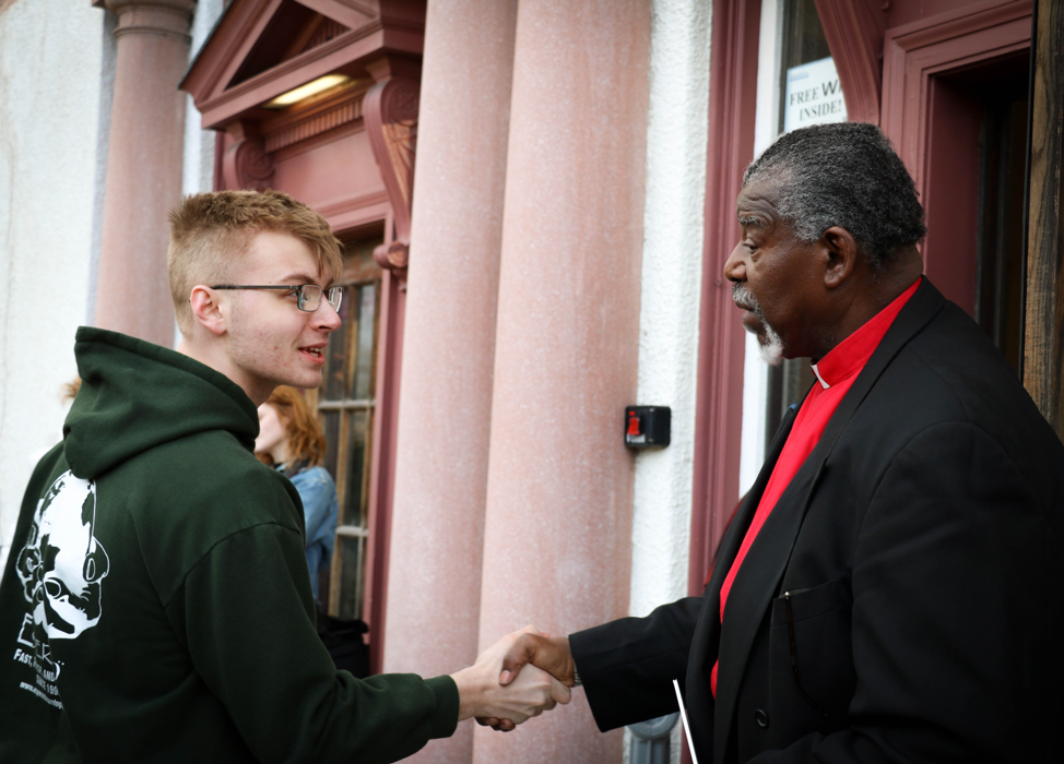 The reverend greets an attendee of the march at the entrance of Bethesda Church.