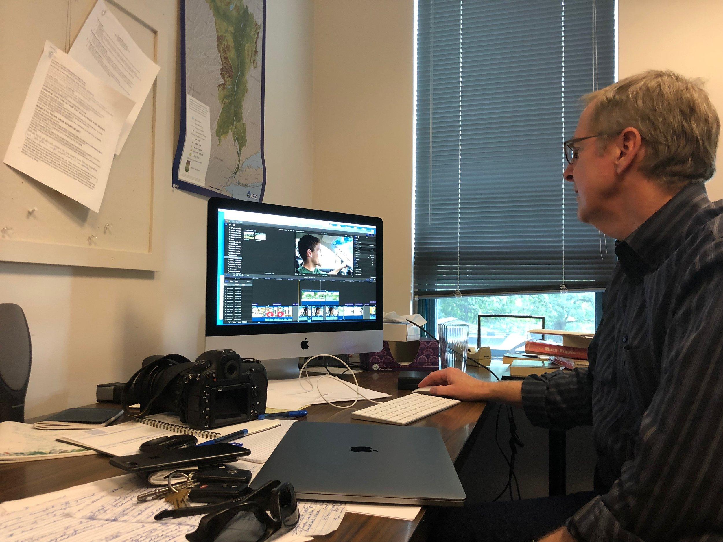 Professor Scarce editing 'Impact' at his desk.