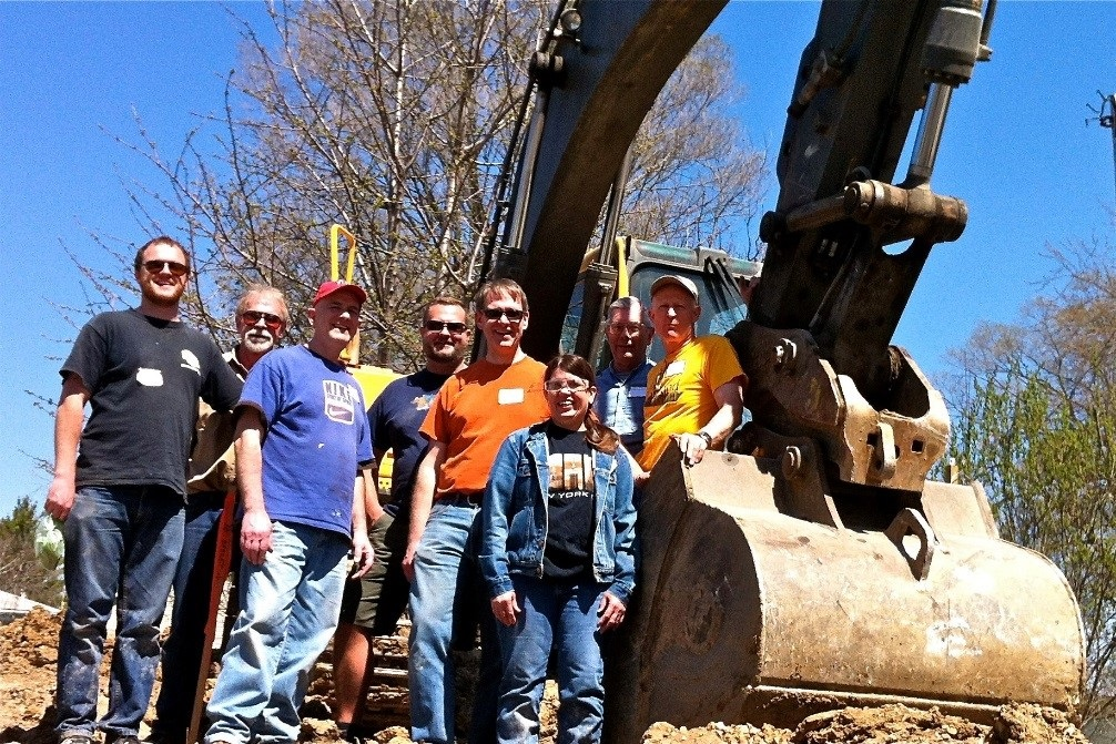 Roger, pictured center wearing an orange shirt and sunglasses, worked with his ManKind Project crew on a Habitat for Humanity service project in April 2015. To his disappointment, he did not get to drive the backhoe.