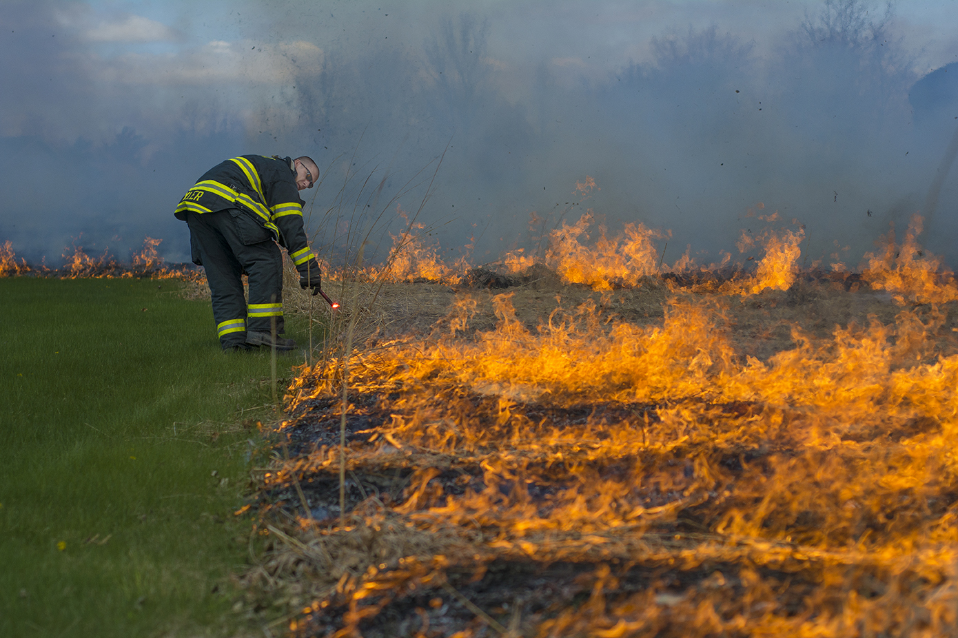A firefighter from the Kent Fire Department uses a road flare to light the prairie grass behind the Student Recreation and Wellness Center on April 28, 2015. The controlled prairie fire is done annually by the department to naturally control the growth of the prairie grasses.