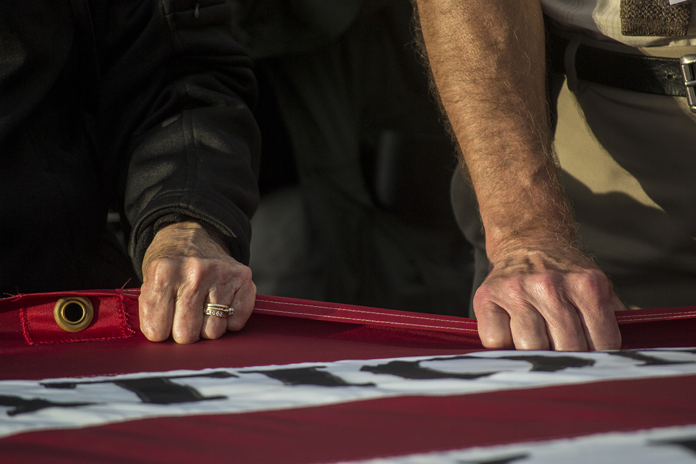 Two visitors to the Flight 93 Memorial in Shanksville, Pennsylvania help to unfold a memorial American Flag that honors the victims of Flight 93. The service was held before a candlelight march and vigil at the memorial on Sept 10, 2014.