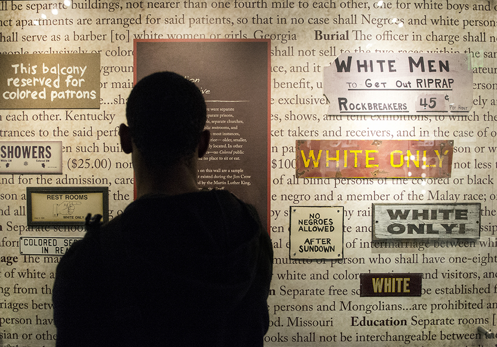 Kenny Jenkins, a communication studies major at Kent State University, stops and stares at a wall inside the Jim Crow Museum of Racist Memorbilia that displays segregation signs and laws created during the Jim Crow Era on Sept 19, 2014. The list of laws, a small sample of thousands,was compiled by the Martin Luther King Jr. National Historic site interpretive staff.  Original story available at    kentwired.com