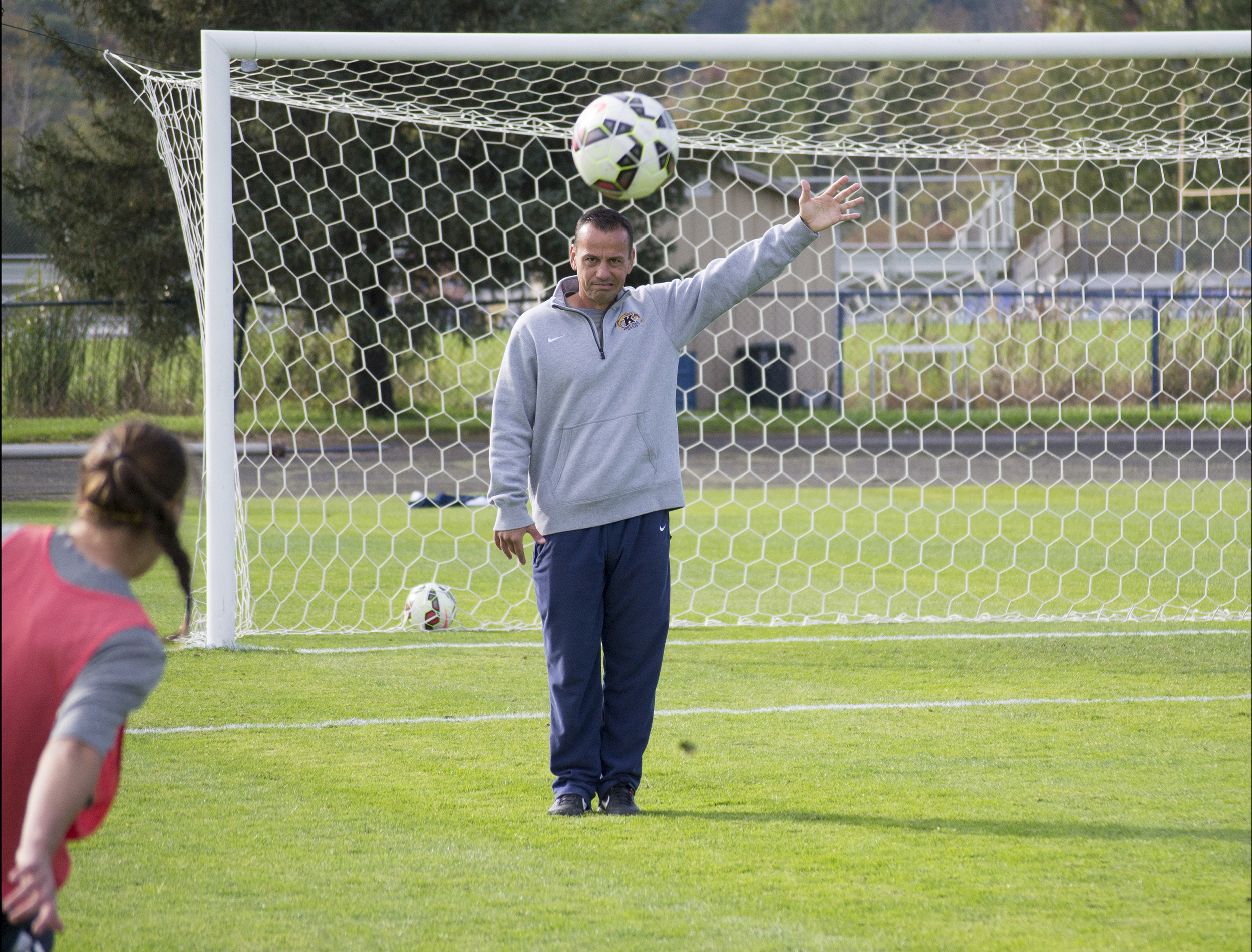Rob Marinaro, head Coach of the Kent State University Women's soccer team, stays late after practice to help one of his free kick specialists,sophomore forward Jenna Hellstrom,at Zoeller Field on Oct. 9, 2014. After teaching them several ways to trick their opponents defense, he acted as a guide for aiming their shots to have the best chance of beating the keeper.