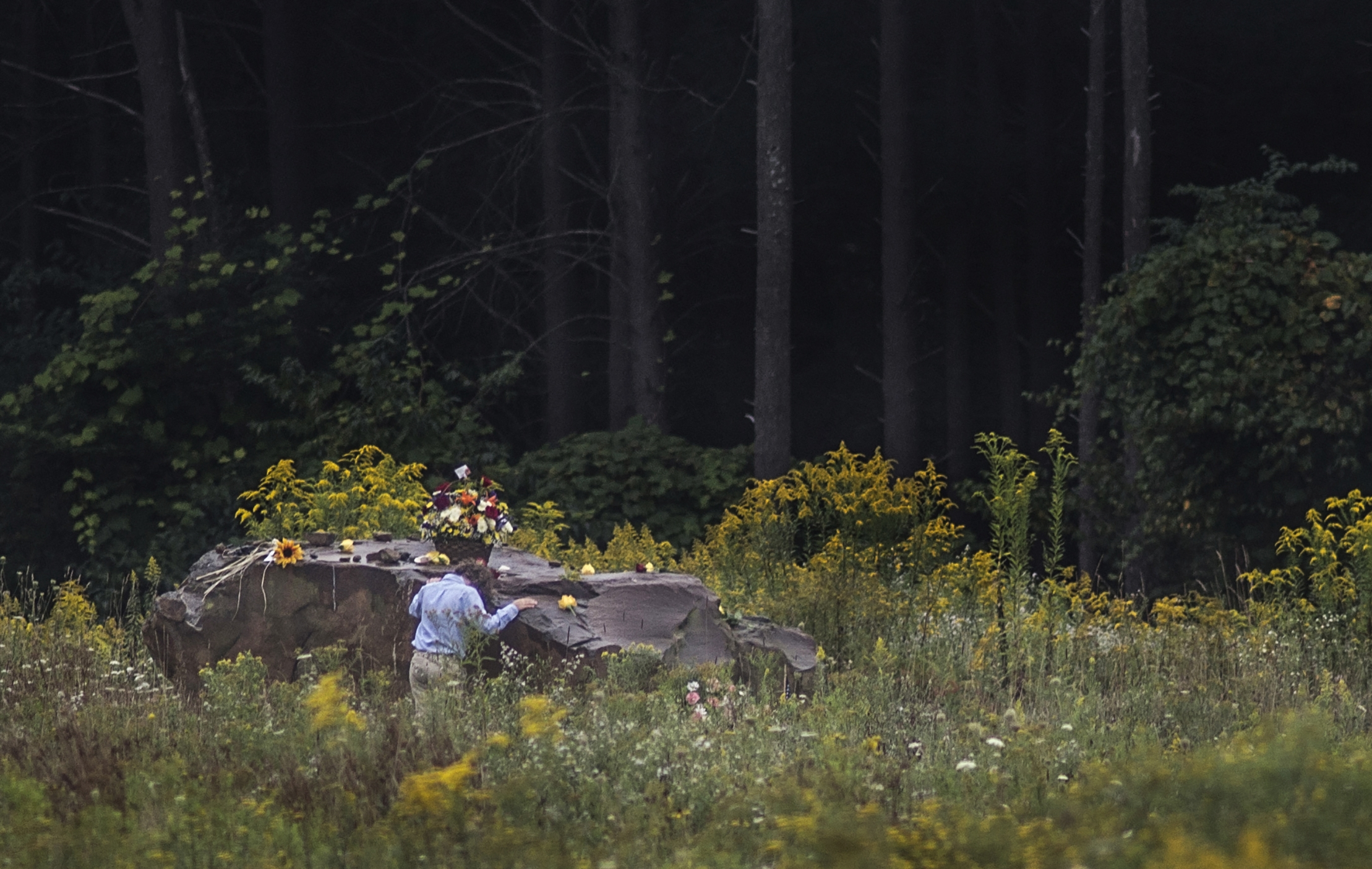 A young family member of one of the 40 victims of Flight 93 rests his head on the boulder that marks where Flight 93 crashed at the Flight 93 National Memorial in Shanksville, Pa. after a Service of Remembrance on Sept. 11, 2014.