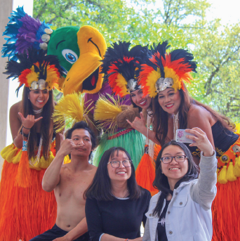 Richland students Luu Nguyen and Ngoc Nguyen takes a selfie with the Hula Grace Dancers, fire showman Tay Kham and the Thunderducks mascot at the 2018 Intercultural Festival on April 11.