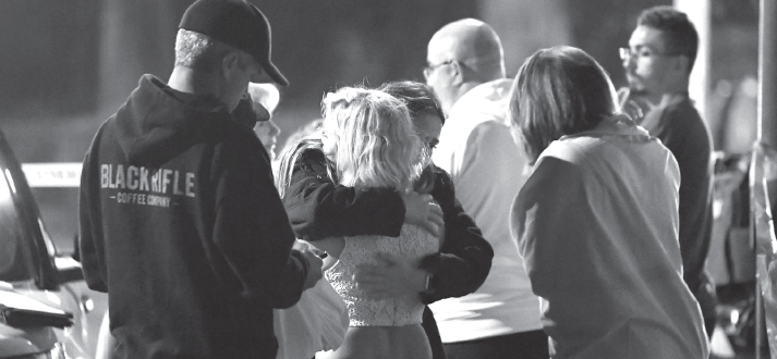 People comfort each other as they stand near the scene of a mass shooting in Thousand Oaks, California where a gunman opened fire inside a country dance bar Nov. 8.