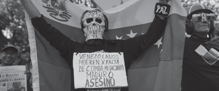 """An anti-government protester wears signs asking for humanitarian aid and a message on his chest that reads in Spanish: """"Venezuelans die for lack of medicines. Maduro is an assassin"""", in Caracas, Venezuela, Feb. 2."""
