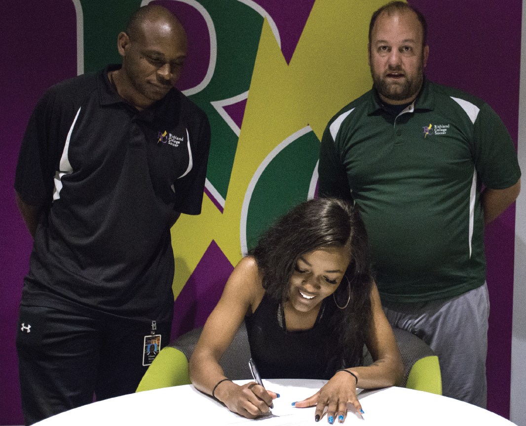Richland women's assistant coach Vinson Brown, left, Alexis Jordan and Head Coach Scott Toups at Jordan's signing on April 10.