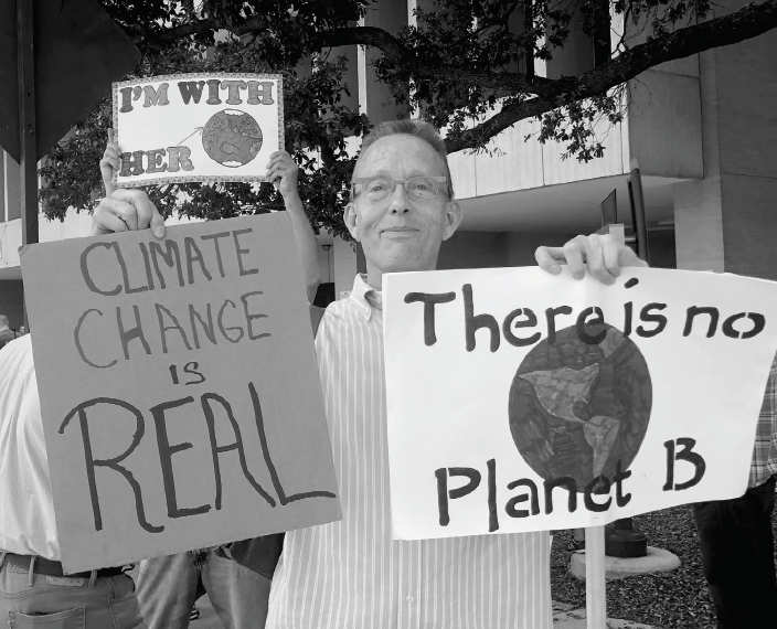 Fort Worth resident Jim Roaten holds climate change protest signs.