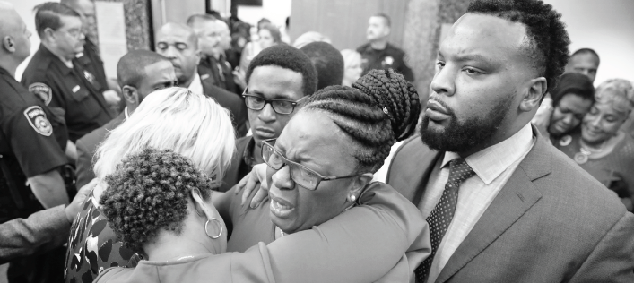 Allison Jean, mother of Botham Jean, is escorted by attorney Lee Merritt and hugged by family members at the conclusion of Amber Guyger's trial in Dallas.