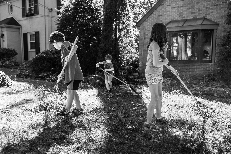 three children raking the front yard