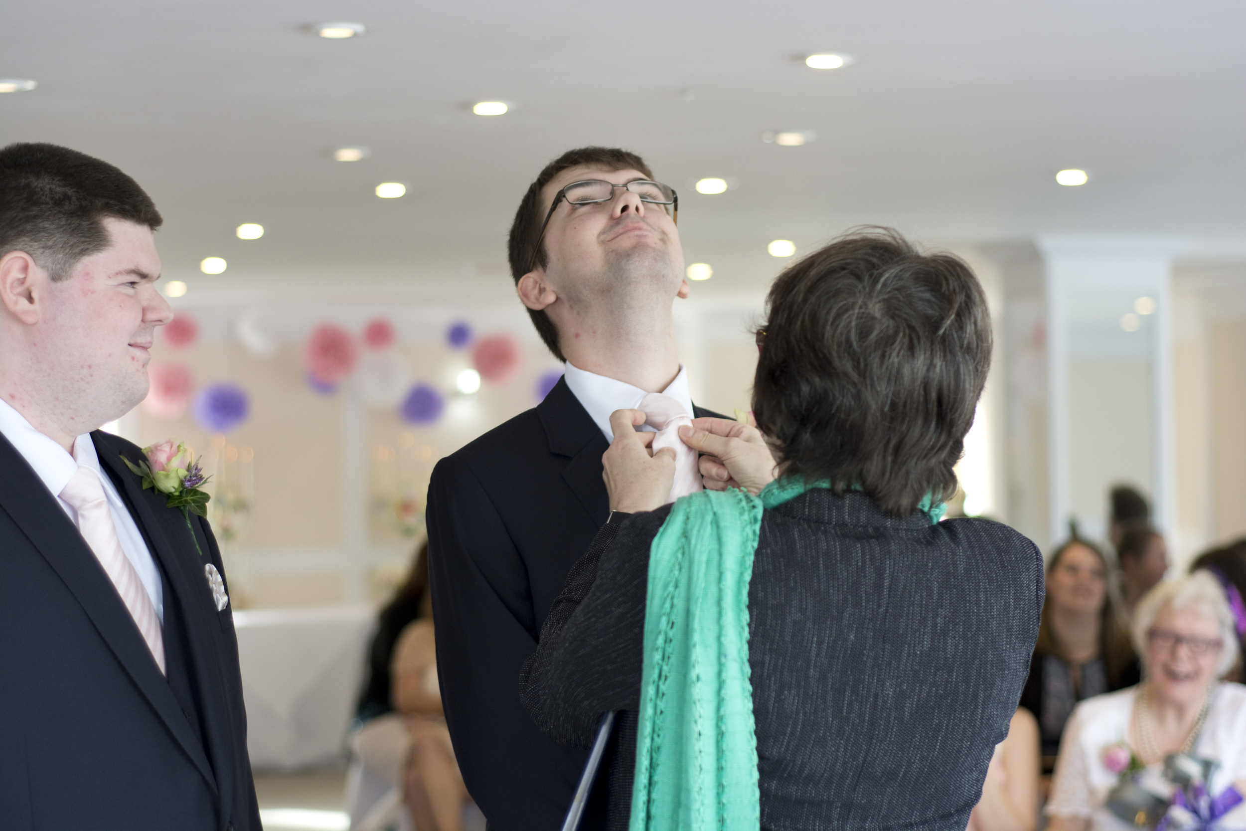 The wedding celebrant adjusts the grooms tie at The GreenBank Hotel Falmouth